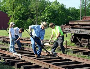 Volunteers lay rail near the new switch for the third display track at the RRHM.  Jeff Smith photo.