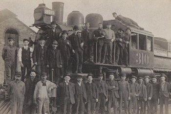 P&R Employees posed for this group photograph in front of a Camelback locomotive.